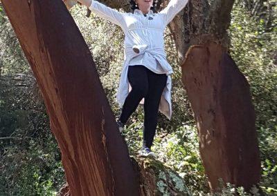 mujer contenta en medio de dos árboles