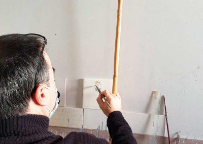 señor pintando un azulejo