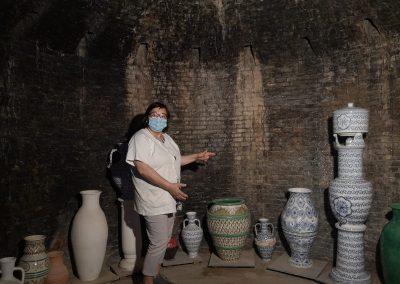 Mujer mostrando jarrones de cerámica