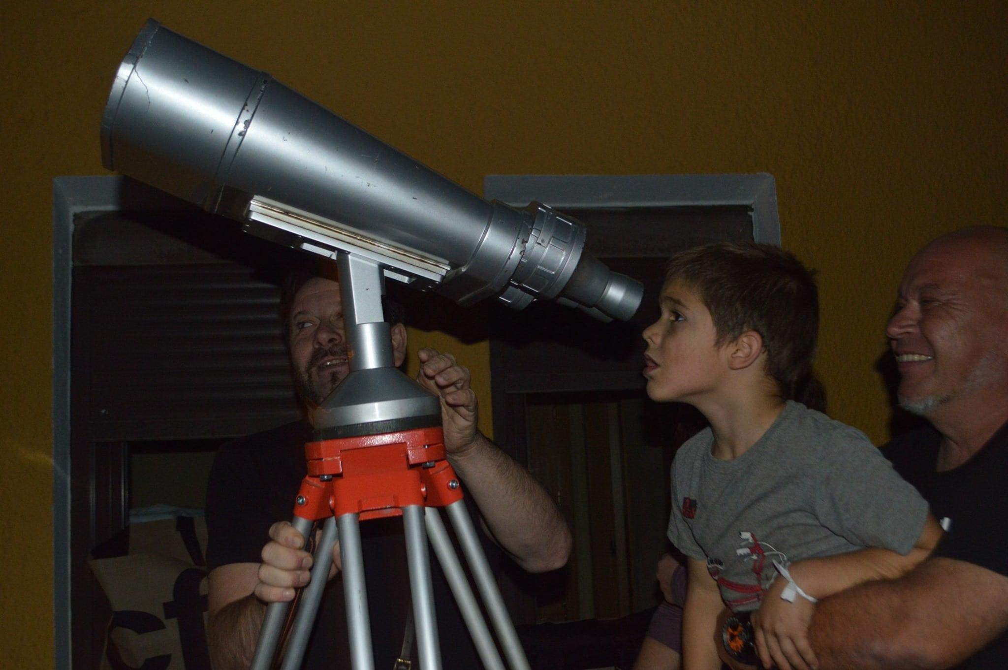 Niño mirando las estrellas a través de un telescopio