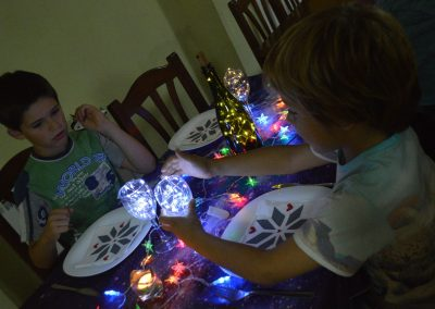 Niños cenando con copas de agua iluminadas