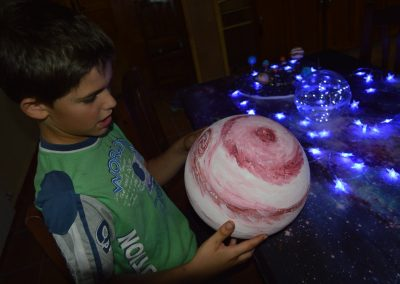 Niño jugando con un planeta ficticio