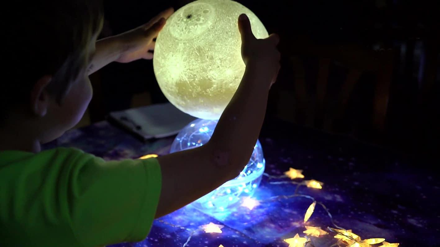 Niño jugando con bolas de luces que simulan estrellas