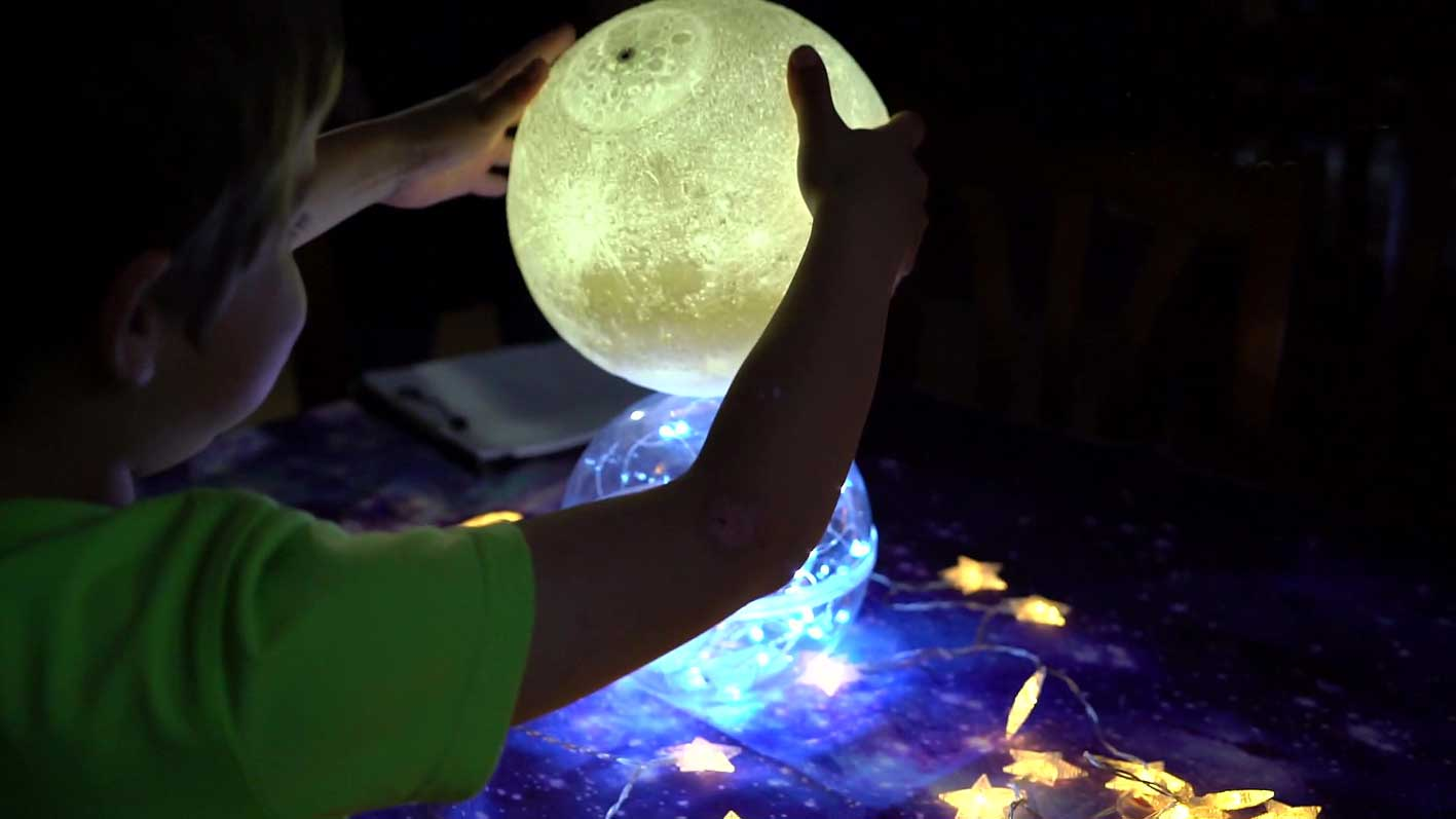 Niño jugando con planetas iluminados